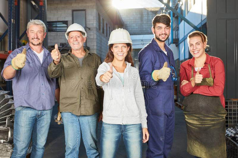 Team of blue collar workers with thumbs up. As motivation royalty free stock photography