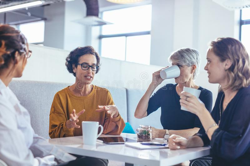 Team brainstorming over new business plan. Group of four business women having a discussion in office. Female professionals sitting around a table and royalty free stock image