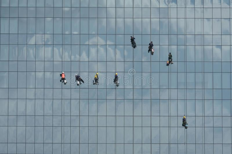 A team of brave men cleaning mirror wall of a very high building. Yesterday I went to a big department store in town far away from home and take pictures royalty free stock images