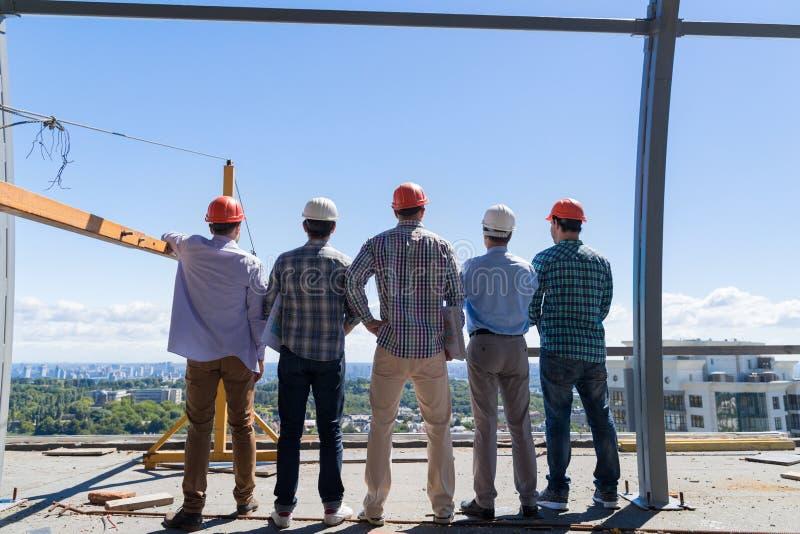 Team Of Builders On Costruction-Plaats Achter Achtermening, het Vennootschap van Voormangroup in hardhat in openlucht en Groepswe royalty-vrije stock foto's
