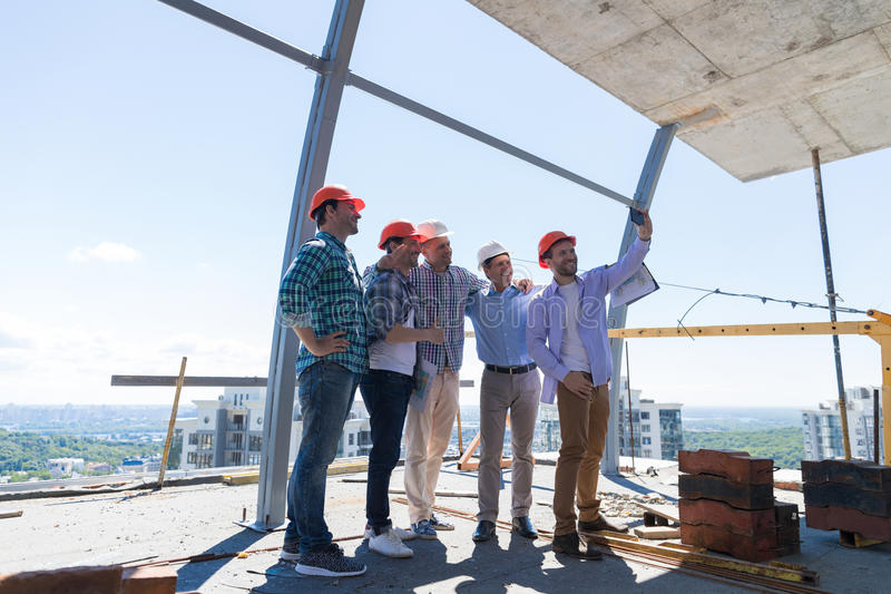 Team Of Builders Happy Smiling Take Selfie Photo During Meeting With Architect And Engineer On Construction Site. Over City View Background royalty free stock images