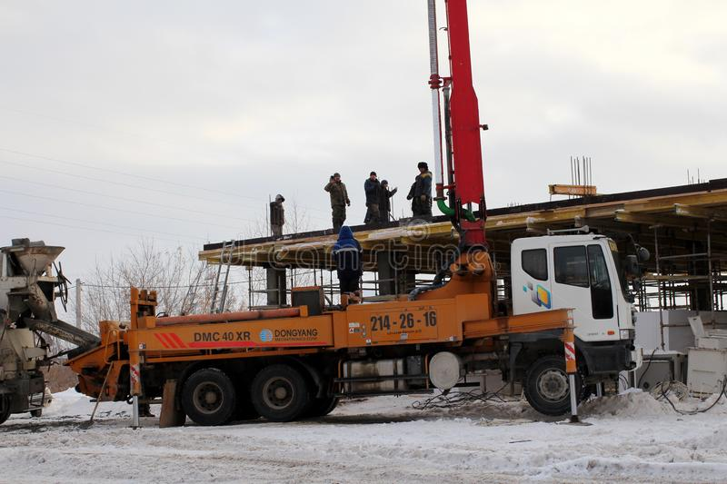 The team of builders working on the construction of the building in Novosibirsk, in the winter of poured concrete using a special royalty free stock photos