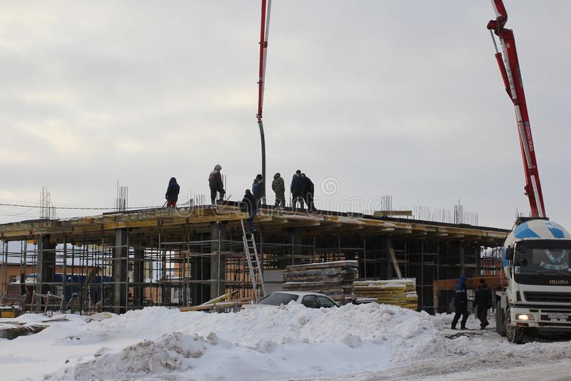The team of builders working on the construction of the building in Novosibirsk, in the winter of poured concrete using a special royalty free stock photo
