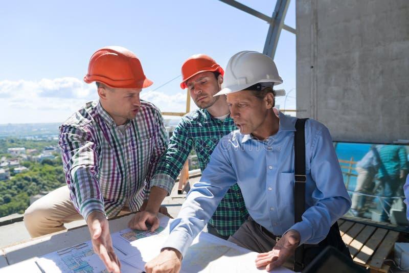 Team Of Builders Working With-Plan auf Standort-Architekten Explain Construction Plan zu Team Og Engineers stockbilder
