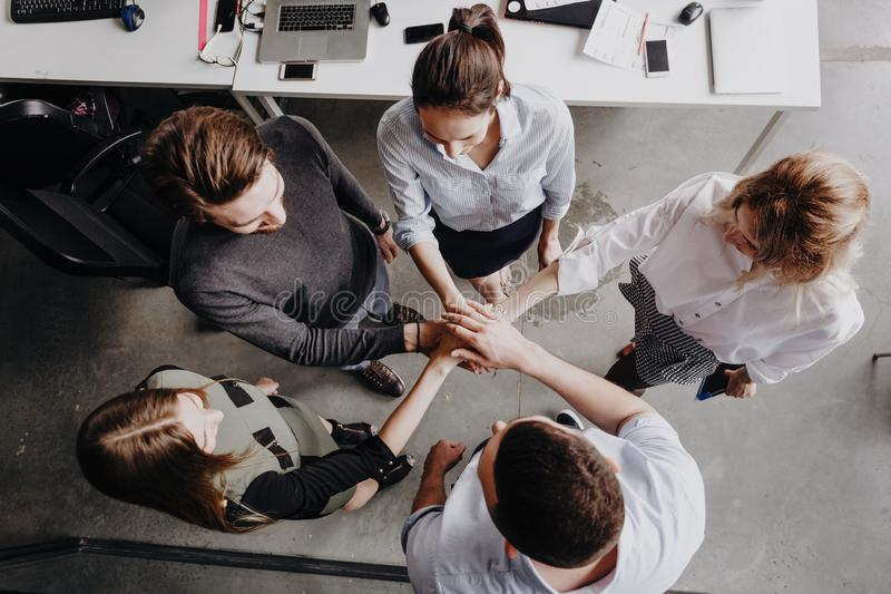 Team Building. The group of colleagues stand in a circle folded their hands together on each other in the modern office. stock photo