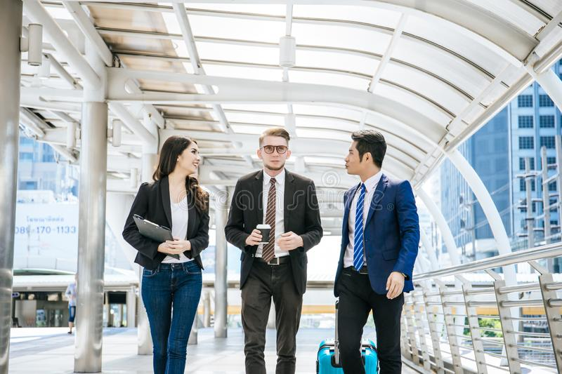 Team of business colleagues meeting while walking in a modern city to go travelling. royalty free stock image