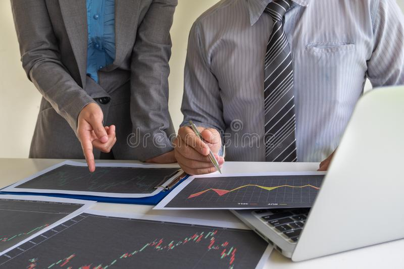 A team of business executives are planning consultations about business investments related to shares. By analyzing and calculating the stock market to find royalty free stock image