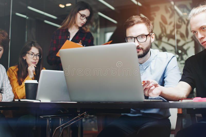 Team of business partners working on laptops in a modern loft room. Laptop typing and new project discussing royalty free stock photos