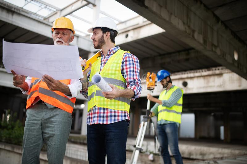 Team of business people in group, architect and engeneer on building site check documents royalty free stock image