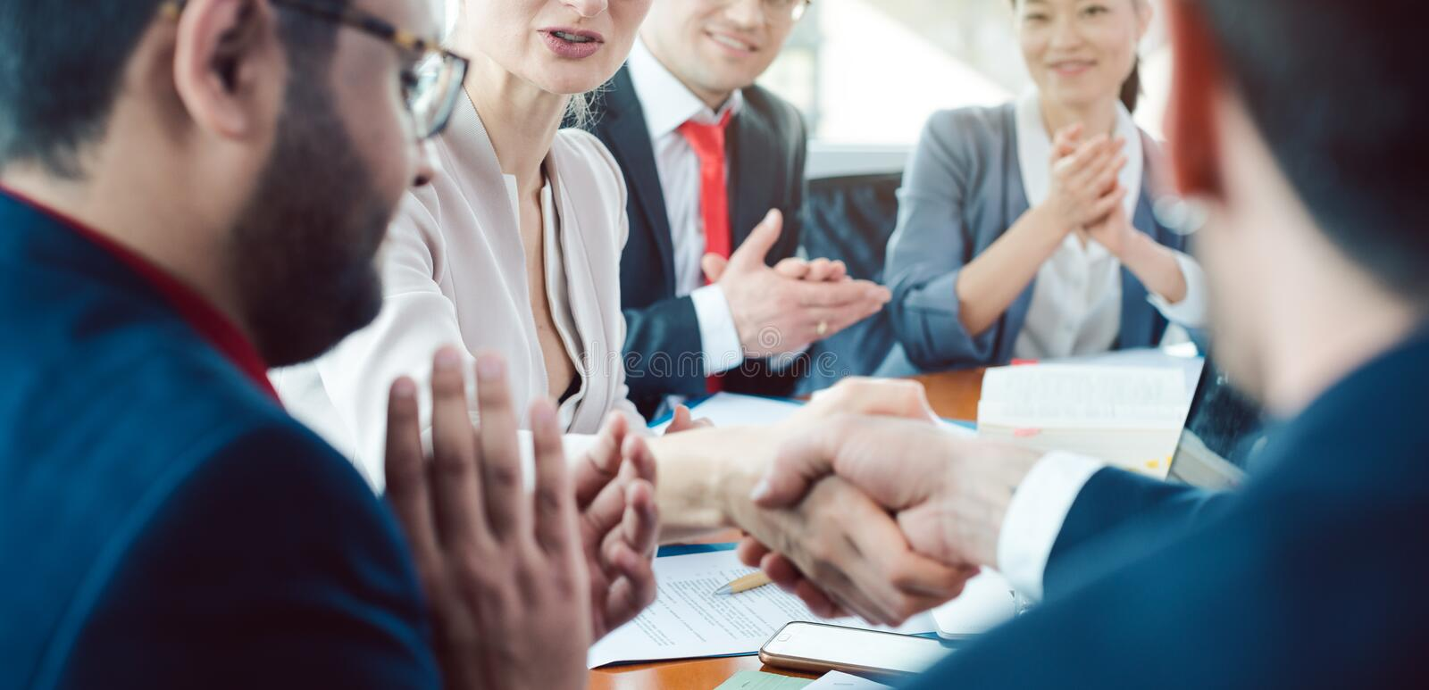 Team of business people negotiating an agreement closing the deal royalty free stock photo