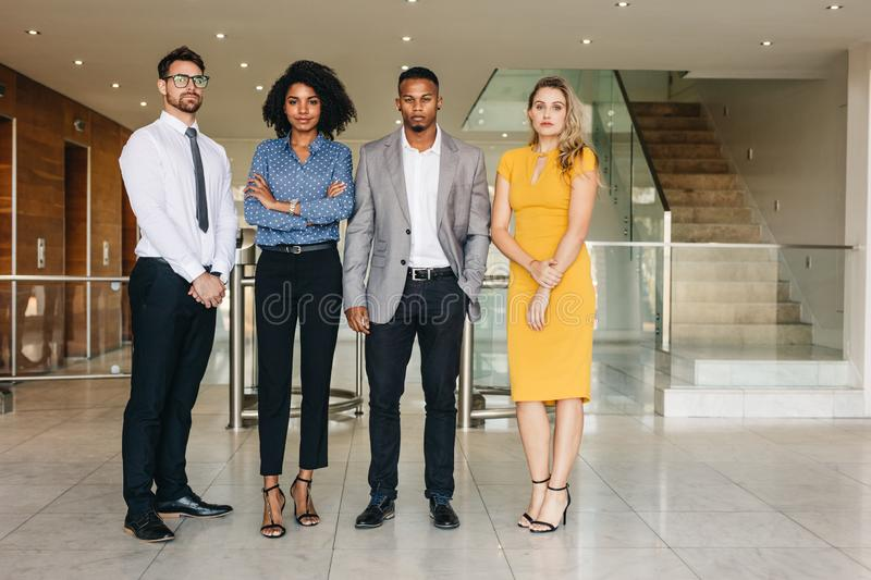 Team of business professionals. Portrait of confident group of business workers standing in office lobby and looking at camera. Businessmen and women together in royalty free stock photography