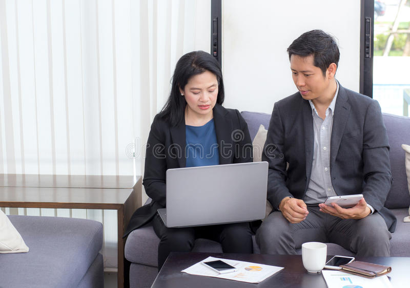 Team of business two people working together on a laptop royalty free stock image