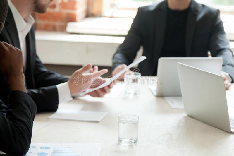Team of businessmen discussing financial statistics report durin. G briefing meeting. CEO holding document with results, project manager consults employees about stock images