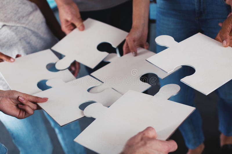 Team of businessmen work together for one goal. Concept of unity and partnership. Team of businessmen work together for one goal with puzzles. Concept of unity stock photo