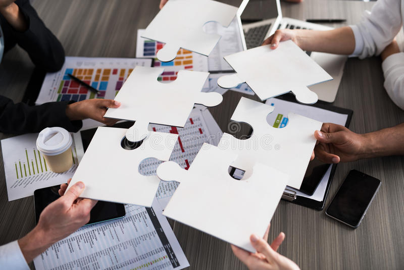 Team of businessmen work together for one goal. Concept of unity and partnership. Team of businessmen work together for one goal with puzzles. Concept of unity stock images
