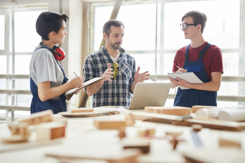 Team of Carpenters Discussing Project stock photography