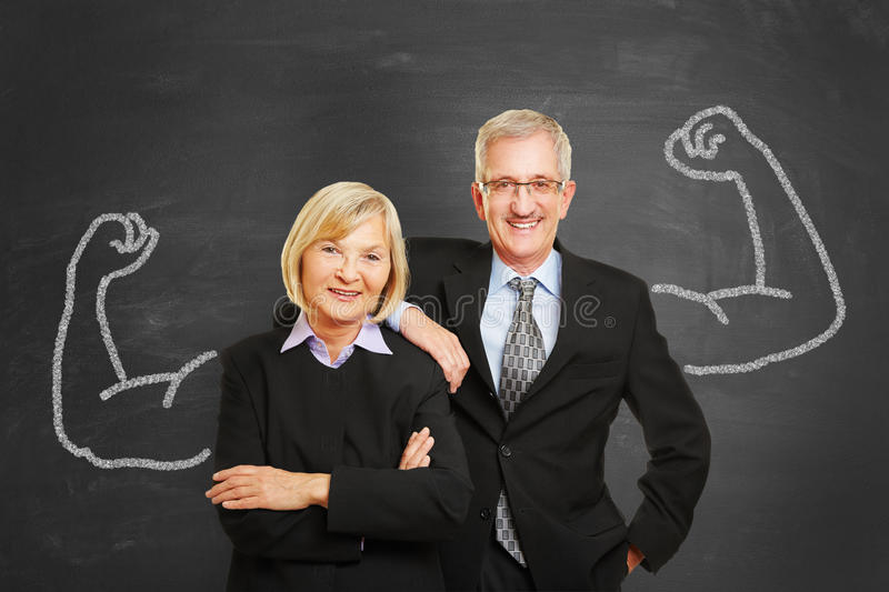 Team with chalk muscles on blackboard stock photos