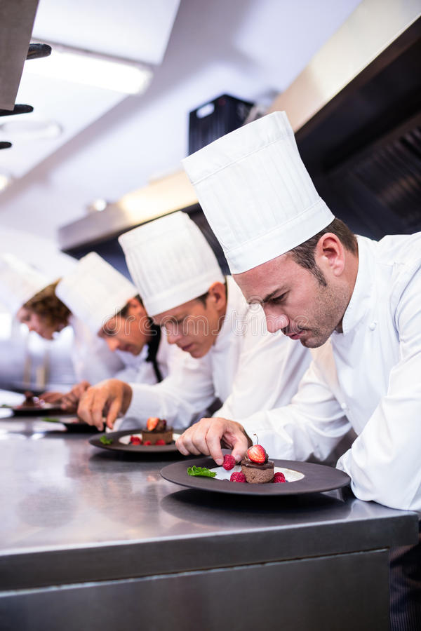 Team of chefs finishing dessert plates in the kitchen stock photos