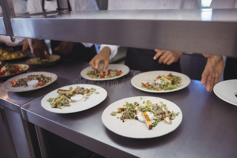 Team of chefs garnishing meal on counter royalty free stock photography