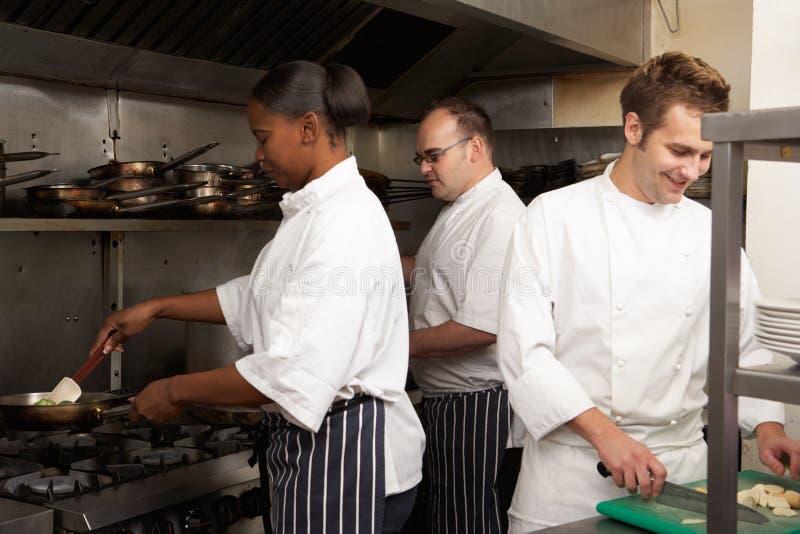 Team Of Chefs Preparing Food. In Restaurant Kitchen stock image