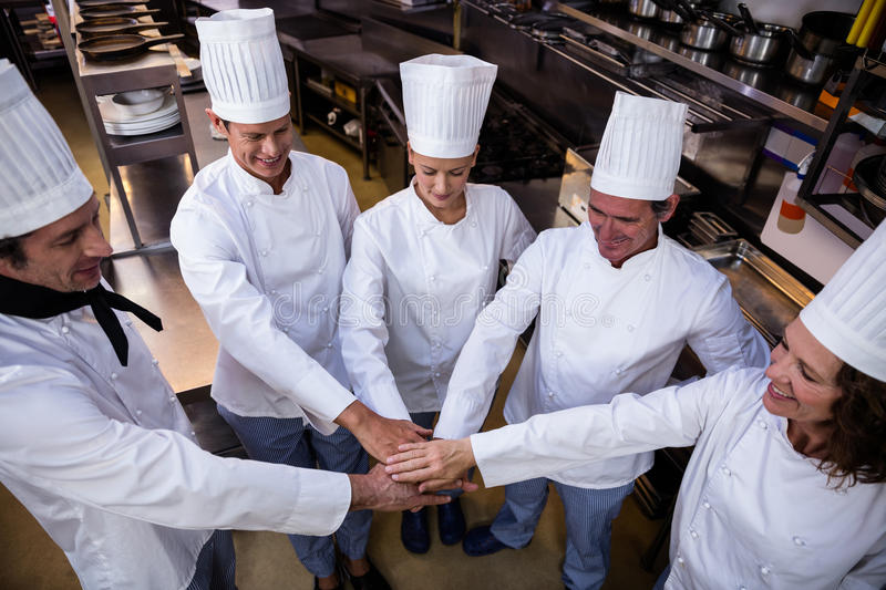 Team of chefs putting hands together royalty free stock photography