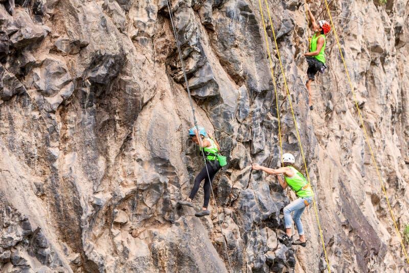 Team Of Climbers Climbing una pared de la roca fotos de archivo