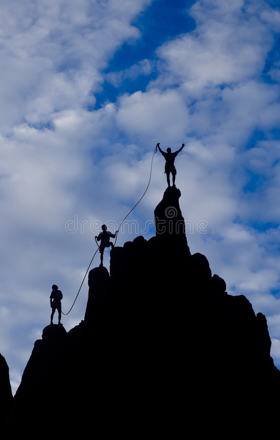 Team of climbers reaching the summit. stock images