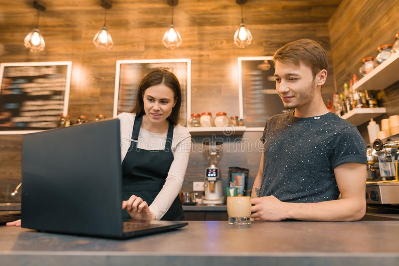 Team of coffee shop workers working near the counter with laptop computer and making coffee, cafe business royalty free stock images