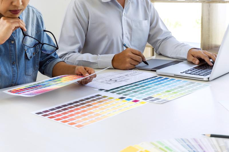 Team of colleague graphic designer drawing and retouching image on graphics tablet and choose color swatch samples for selection royalty free stock photos