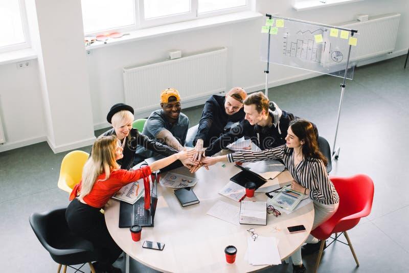 Team Communication Hoogste meningsdeel van groep van zes jongeren die in vrijetijdskleding iets bespreken met glimlach terwijl royalty-vrije stock foto's