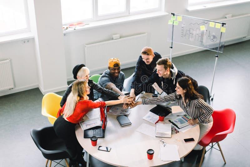 Team Communication Parte di vista superiore di un gruppo di sei giovani nell'abbigliamento casual che discutono qualcosa con l'at immagini stock