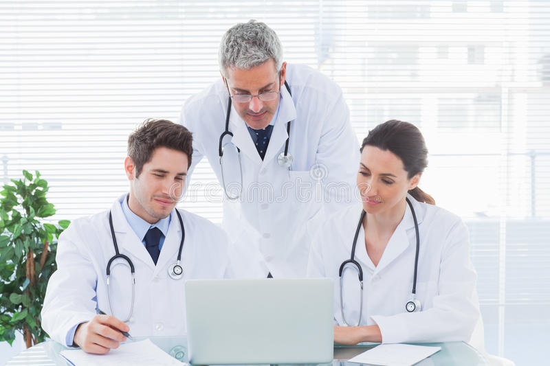 Team Of Concentrated Doctors Working Together With Their Laptop ...
