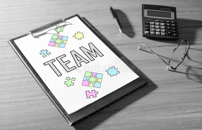 Team concept on a desk. Team concept on a clipboard with a calculator stock photo