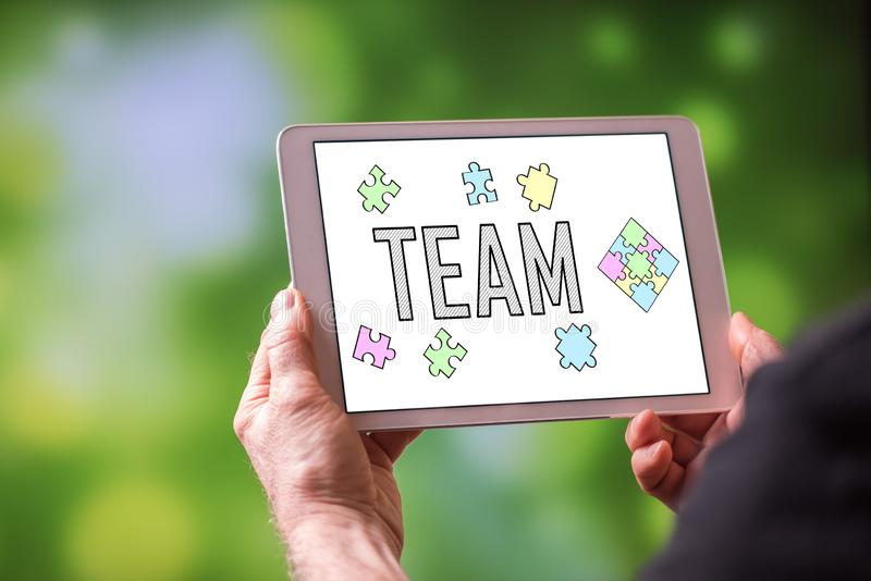 Team concept on a tablet. Man holding a tablet showing team concept royalty free stock photos