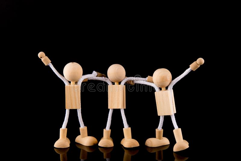 Team concept, Wooden Stick Figures team isolated on black background. stock photo