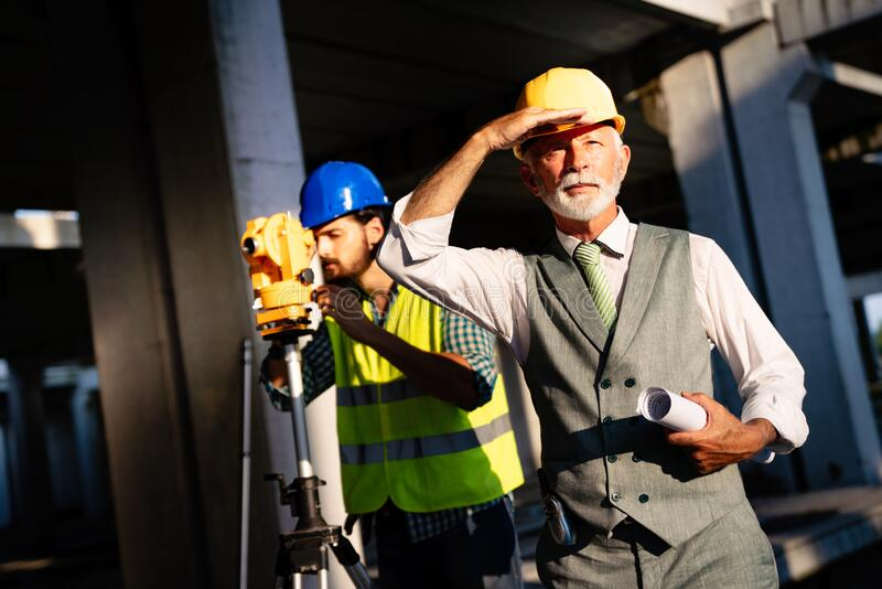 Team of construction engineers, architects working on building site stock photos