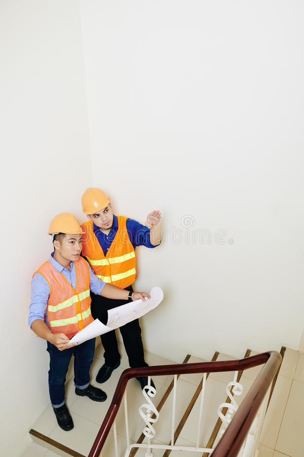 Contractors discussing flight of stairs stock photo