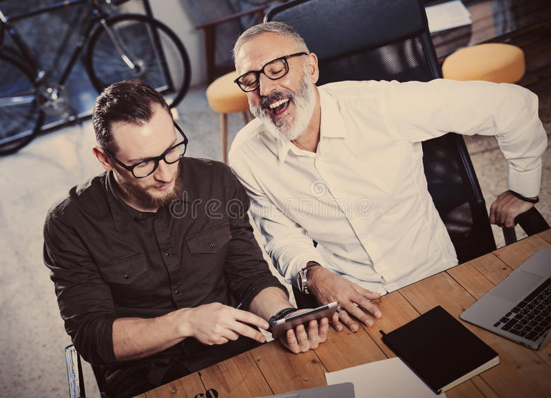 Team of coworkers making great time brake during work discussion in modern office.Adult bearded man watching mobile stock photos