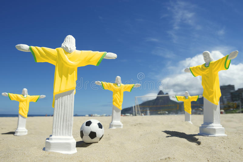 Team of Cristo Football Players Ipanema Beach Rio. Team of religious figurines in yellow uniforms playing a game of beach football kicking soccer ball on Ipanema royalty free stock photo