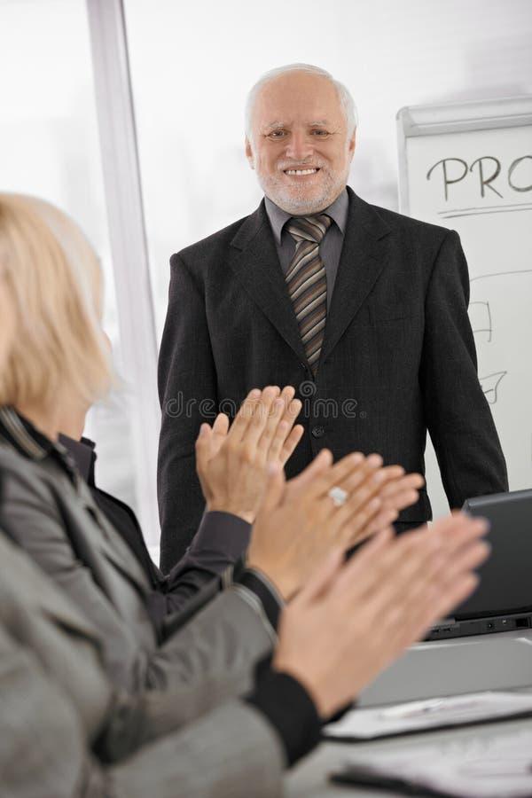 Team, das älteren Geschäftsmann im Büro applaudiert stockfoto