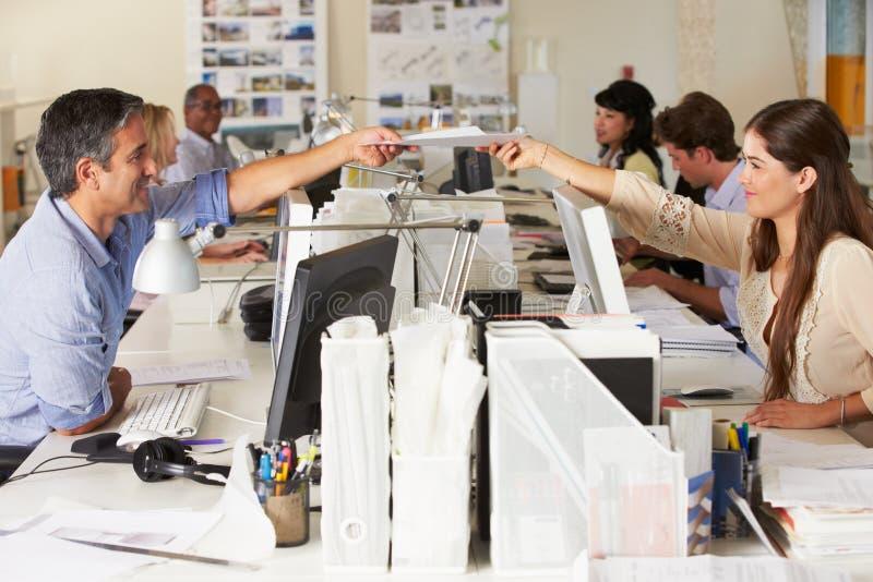 Team, das an den Schreibtischen im besetzten Büro arbeitet stockbilder