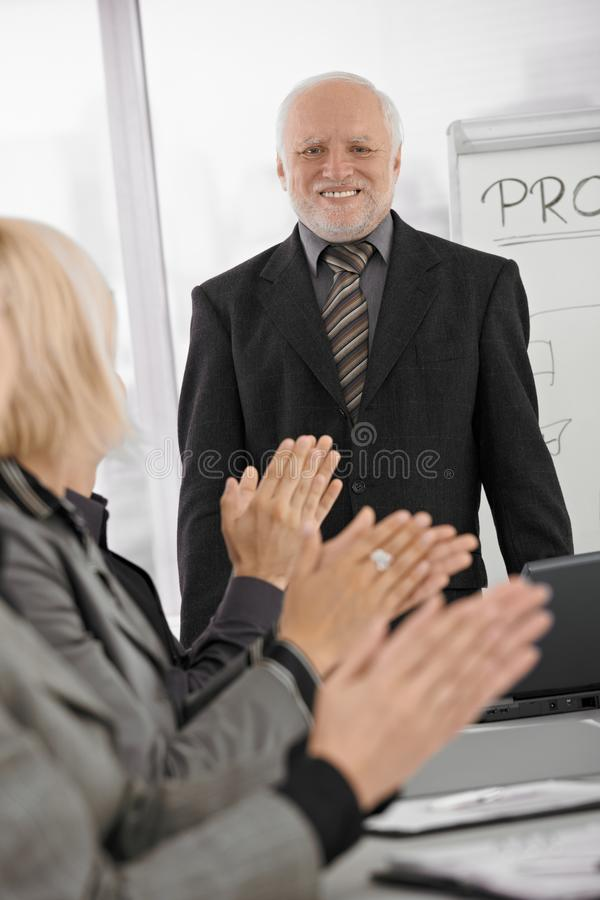 Team dat hogere zakenman in bureau toejuicht stock foto