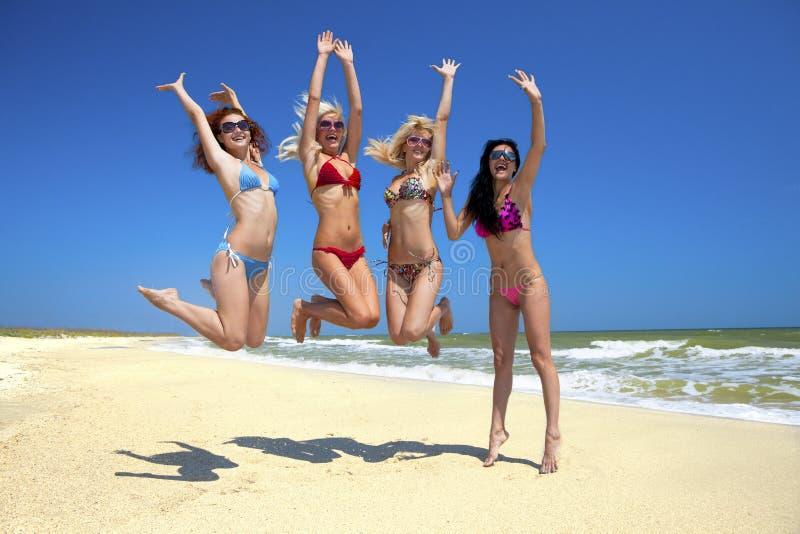 Team der Freunde, die am Strand springen stockfotografie