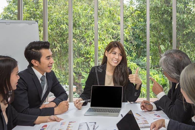 Team des asiatischen Geschäfts aufwerfend im Konferenzzimmer Arbeitendes in einem Raum auf dem Tisch gedanklich lösen Asiatische  stockfoto
