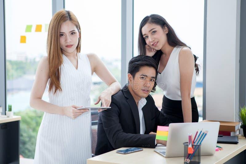 Team des jungen Geschäftsmannes und zwei Geschäftsfrau, das zusammen mit Laptop-Computer auf Schreibtisch im Büro arbeitet Chef c lizenzfreie stockfotos