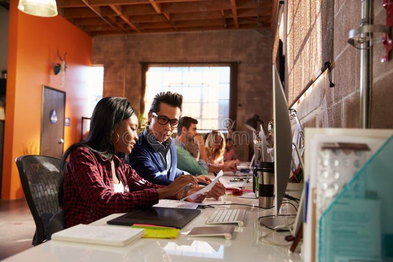 Team Of Designers Working At skrivbord i modernt kontor royaltyfria foton