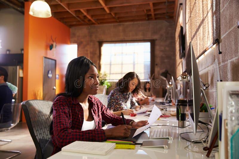 Team Of Designers Working At skrivbord i modernt kontor arkivfoton