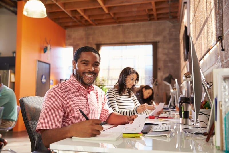 Team Of Designers Working At skrivbord i modernt kontor arkivbild