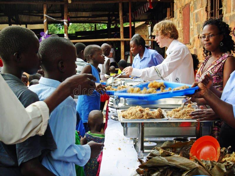 Team die Freiwilligen Arbeitskräfte der Hilfsentlastung, die hungrigen Kindern Afrika einziehen lizenzfreie stockfotografie