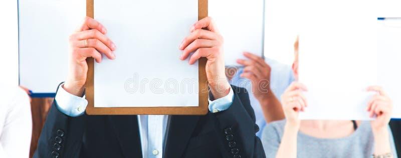 Team die van zakenlui omslagen houden dichtbij gezicht op witte achtergrond stock afbeeldingen